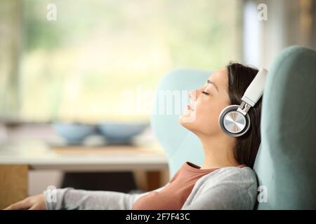 Vista lateral retrato de una mujer relajada con auriculares inalámbricos escuchar música en una silla de ala