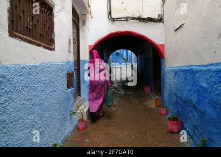 Mujer con vestido rosa caminando en un callejón poco colorido en la medina de Tetuán, al norte de Marruecos, África