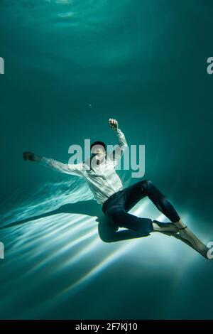 Hombre árabe con ropa formal sentado en la parte inferior de la piscina piscina