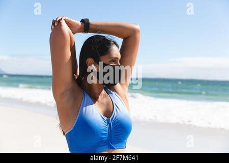 Mujer de raza mixta haciendo ejercicio en la playa con máscara y brazos de estiramiento de auriculares inalámbricos