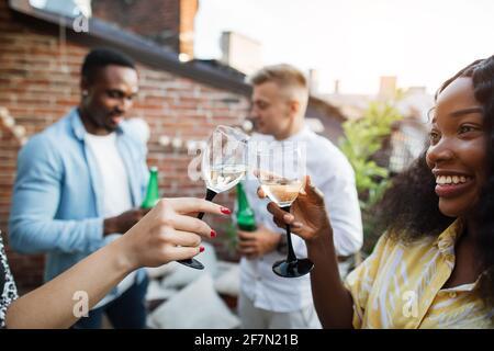 Cerca de dos mujeres toasting con copas de champán mientras dos hombres bebiendo cerveza y charlando en el fondo. Cuatro amigos de carreras mixtas disfrutando de una fiesta en la azotea.