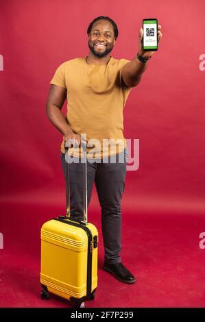 Feliz hombre africano de pie con un pequeño y elegante bolso y teléfono móvil en sus manos, utilizando código QR para el control de paso rápido y seguro y las costumbres, teniendo un billete en línea, viajar con el concepto de comodidad