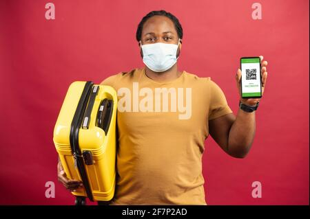 Feliz hombre africano en máscara médica de pie sobre el fondo rojo sosteniendo un bolso amarillo para viajar y celular con código QR en la pantalla, concepto de visualización de boletos sin contacto, paso seguro de aduanas