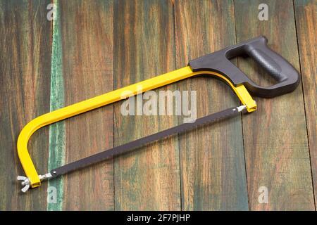 Arco de sierra, herramientas de mano para serrar, aisladas sobre fondo de madera