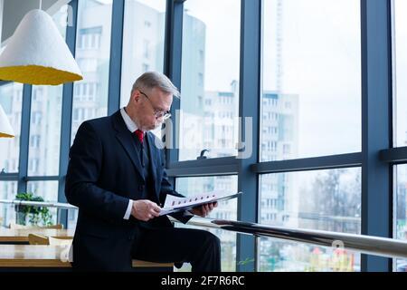 El director general del hombre se inclinó sobre una mesa de madera en su oficina cerca de una ventana grande y observa un plan de desarrollo empresarial exitoso.