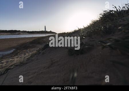 Hermoso tiro de la costa cerca de un faro bajo un cielo azul claro Foto de stock
