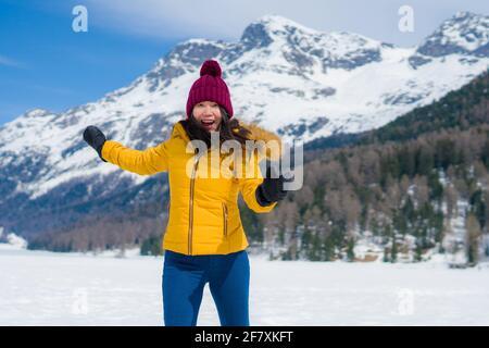 Joven feliz y alegre mujer coreana asiática en chaqueta de invierno y sombrero corriendo juguetón en un lago helado cubierto de nieve En las montañas de los Alpes suizos disfrutando h