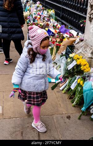 Buckingham Palace, Londres, Reino Unido. 10th de Abr de 2021. Un niño pone flores fuera del Palacio de Buckingham en memoria del Duque de Edimburgo (Príncipe Felipe) que falleció el 9th de abril. Crédito: Grant Rooney/Alamy Live News