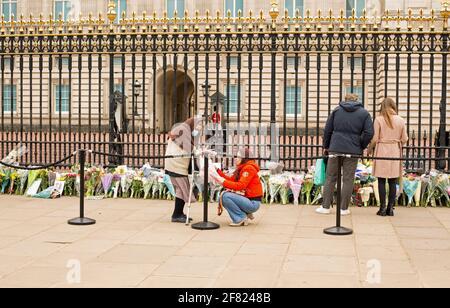 Buckingham Palace en Londres, Miembros del público que ponen flores por la muerte del príncipe Felipe, el duque de Edimburgo. Londres, Reino Unido, 10th de abril de 2021