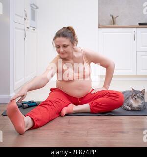 Una mujer embarazada hace ejercicio en una cocina casera y. se estira con su mano a su pierna mientras está sentada el suelo