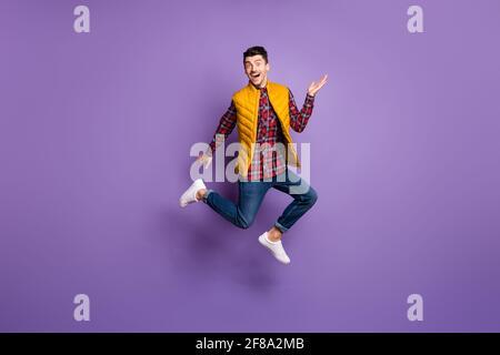Foto de perfil a tamaño completo de un hombre optimista ropa de salto camisa jeans chaleco aislado sobre fondo color violeta