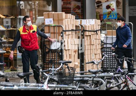 Berlín, Alemania. 12th de Abr de 2021. Un mensajero que lleva una máscara lleva paquetes en Berlín, capital de Alemania, el 12 de abril de 2021. Más de tres millones de infecciones por COVID-19 se han registrado en Alemania el lunes desde el brote de la pandemia, según el Instituto Robert Koch (RKI). Crédito: Stefan Zeitz/Xinhua/Alamy Live News