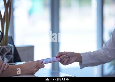La recepcionista entrega un pasaporte a un turista en te recepción y recepción de un albergue