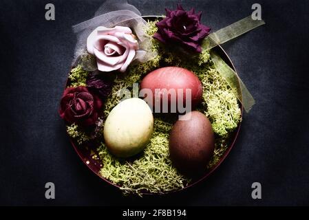 huevos de pascua teñidos en un tazón decorativo con musgo y. rosas