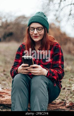Una chica de viaje con ropa de cintura baja se sienta en un tronco disfrutando, relajándose en el bosque cerca del camping. Mujer con smartphone