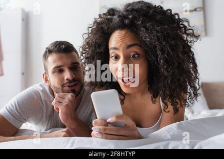 mujer afroamericana sorprendida sosteniendo un smartphone cerca de un novio barbudo fondo borroso