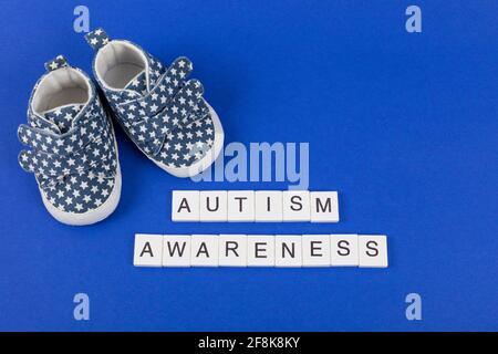 Conocimiento del autismo. Calzado deportivo infantil con inscripción Autism Awareness sobre fondo azul. Capa plana. Espacio de copia. Foto de stock