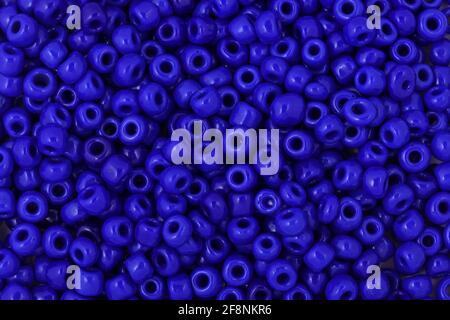 Cuentas azules sobre el fondo blanco primer plano, macro, hacer collar de abalorios