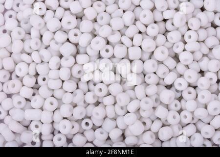 Cuentas blancas sobre el fondo blanco primer plano, macro, hacer collar de abalorios