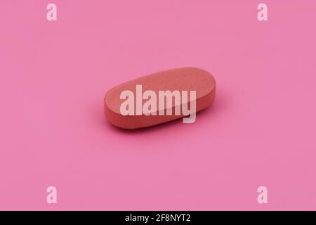Forma ovalada tableta de medicina farmacéutica sobre fondo rosa, Lay plano espacio de copia conceptos de medicina bebé color rosa fondo
