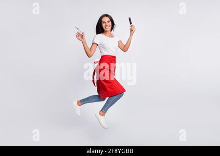 Foto de perfil de tamaño completo de bonito morena optimista largo cabello señora con tijeras saltar llevar camiseta blanca aislada en gris color de fondo