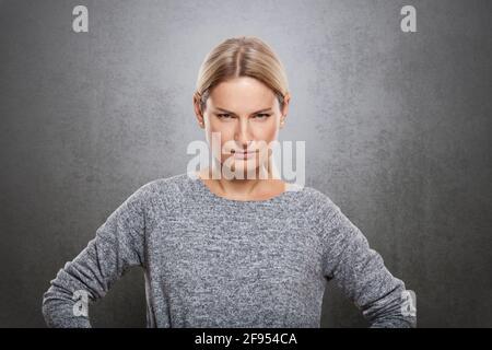 Retrato de una mujer muy estricta está mirando la cámara. Sobre un fondo gris concreto., El retrato de una mujer muy estricta está mirando la cámara. Encendido