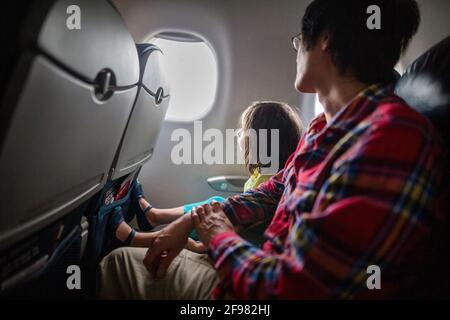 Una niña y un padre se sientan juntos en el avión mirando fuera de la ventana