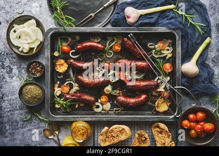 Vista superior de las deliciosas salchichas a la parrilla servidas con cebolla, tomates, ajo, pan y hierbas