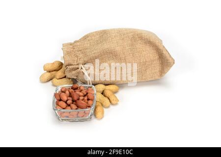 Cacahuetes. Saco de yute burlap lleno de cacahuetes y tazón de vidrio con granos pelados. Aislado sobre fondo blanco.