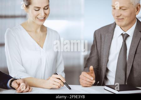 Empresario de edad avanzada y grupo de empresarios que discuten contrato en el cargo. Mujeres y abogados trabajando juntos en la reunión. Trabajo en equipo y.