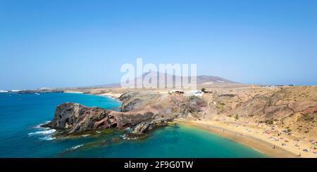 Playa Blanca, Lanzarote, Islas Canarias, España. Vista panorámica a lo largo de la costa desde el acantilado sobre Playa del Papagayo, Atalaya de Femés en el fondo.