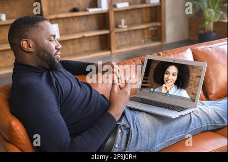 Vista lateral de los gestos concentrados de hombre de piel oscura joven con las manos mientras se realiza una videollamada en el portátil con un amigo, una niña, un compañero o un compañero de negocios tumbado en el sofá de su casa, explicando su idea