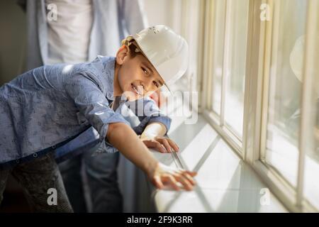 Adolescente que mide la longitud del alféizar de la ventana con una regla de cinta, con casco blanco y sonriendo