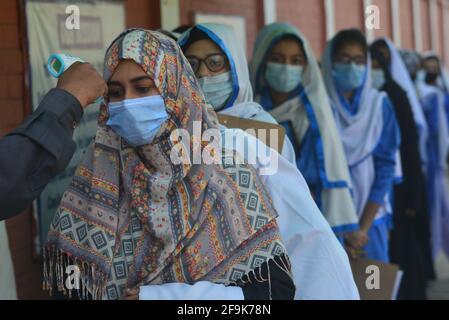 Lahore, Pakistán. 19th de Abr de 2021. Un guardia de seguridad está revisando la temperatura corporal y desinfectando los zapatos de las niñas estudiantes antes de entrar en los Institutos educativos. Gobierno Kinaird niñas escuela secundaria de 9th a 12th grados está reabierto después de largas vacaciones debido a la tercera fase de Covid-19 en Lahore. (Foto de Rana Sajid Hussain/Pacific Press) Crédito: Pacific Press Media Production Corp./Alamy Live News