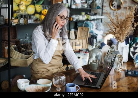 Vendedor profesional con pelo gris sentado en la tienda de decoración con ordenador portátil abierto y hablando en móvil. Mujer anciana usando aparatos modernos en el trabajo.