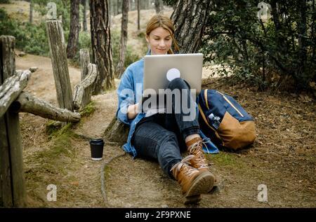 Mujer joven sentada en el suelo en el bosque y trabajando en un ordenador portátil .