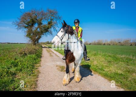 Joven montando a caballo en un camino rural a través del campo en un día soleado en primavera en West Sussex, Inglaterra, Reino Unido. Jinete de caballo.