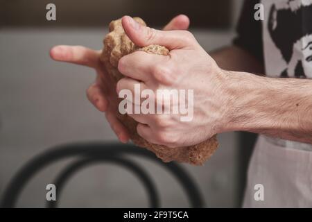 Hombre caucásico joven irreconocible en el delantal amasando la masa en una cocina. Él está haciendo pan.