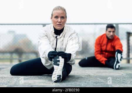 Atletas masculinos y femeninos haciendo ejercicio de estiramiento en el parque público