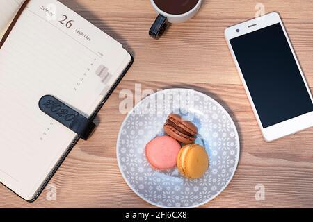 foto cenital de sabrosas macarrones, taza de café, diario y teléfono móvil sobre una mesa de madera