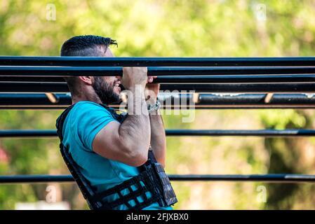 Hombre de pelo oscuro con barba haciendo un tirón en barra calistenia con chaleco de peso. Concepto de gimnasio al aire libre. Foto de stock