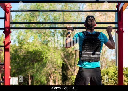 Vista trasera de un hombre morena con barba haciendo un tirón de la barbula con chaleco de peso. Concepto de gimnasio al aire libre. Foto de stock