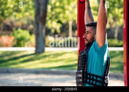 Hombre morena barbudo haciendo un tirón de la barbula con chaleco de peso. Concepto de gimnasio al aire libre. Foto de stock