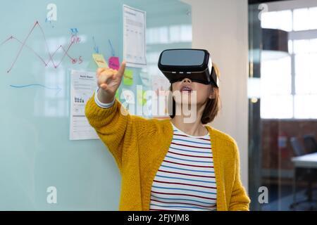 Mujer de negocios asiática de pie delante de la pizarra que lleva realidad virtual auriculares