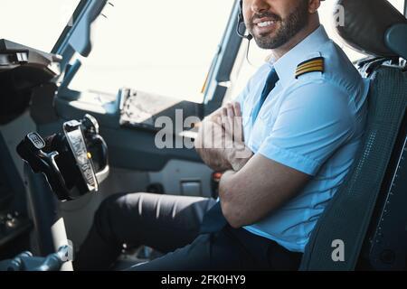 Contento guapo piloto en su lugar de trabajo durante el día