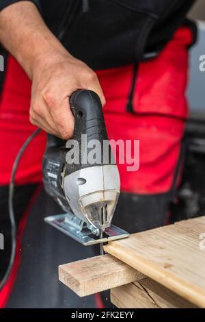 Cerca a mano de carpintero desconocido trabajando con un corte eléctrico de madera con el concepto de la manía de la madera de la sierra espacio