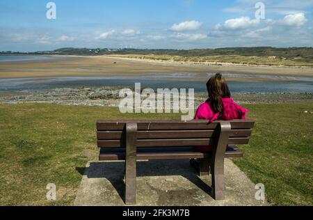 Señora mirando al otro lado del estuario del río Ogmore en Ogmore by Sea en la Costa de la Herencia de Glamourgan, al sur de Gales