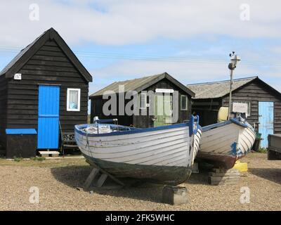 Cabañas de pescadores tradicionales de madera negra a lo largo del puerto Southwold con sus puertas pintadas de colores brillantes, con barcos de pesca en los accesorios de madera. Foto de stock
