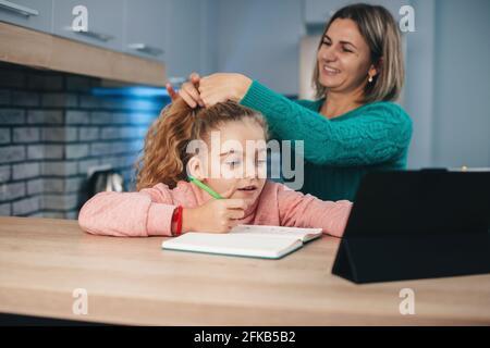 La madre caucásica está arreglando el pelo de la muchacha mientras ella está teniendo clases en línea con una tableta