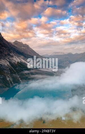Nubes al atardecer sobre el prístino lago Oeschinensee en la niebla, Oberland bernés, Kandersteg, cantón de Berna, Suiza, Europa Foto de stock